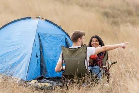 Photo for Man pointing away near smiling african american woman with cup during camping outdoors - Royalty Free Image