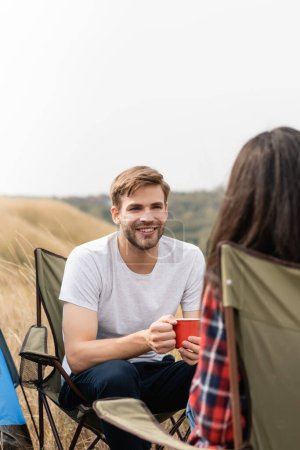 Smiling man with cup looking at girlfriend on chair on blurred foreground during camping