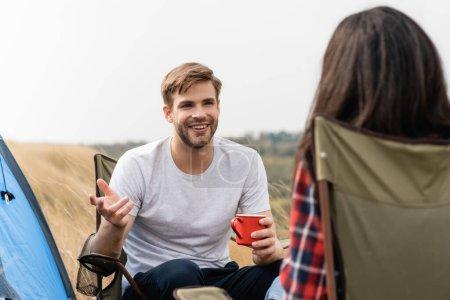 Lächelnder Mann mit Tasse im Gespräch mit Freundin auf verschwommenem Vordergrund beim Zelten