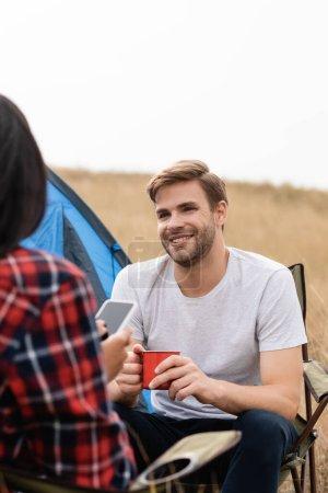 Hombre sonriente sosteniendo taza cerca de novia afroamericana con teléfono inteligente en primer plano borroso durante el camping