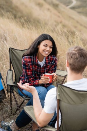 Positive african american woman with cup sitting near boyfriend during camping on grassy field