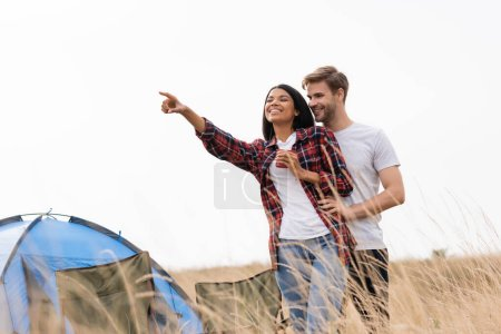 Photo for Smiling man hugging african american girlfriend with cup pointing with finger near chairs and tent on grassy lawn - Royalty Free Image