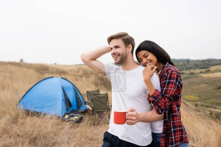 African american woman with closed eyes hugging boyfriend with cup near tent on blurred foreground