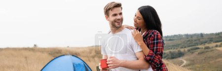 Photo for African american woman smiling and hugging boyfriend with cup near tent on blurred background outdoors, banner - Royalty Free Image
