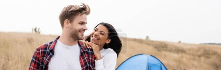 Photo for Smiling man looking at african american girlfriend with tent and field on blurred background, banner - Royalty Free Image