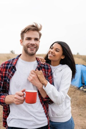 Cheerful multiethnic couple with cup holding hands with tent on blurred foreground outdoors