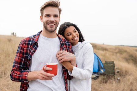 Smiling african american woman holding hand of boyfriend with cup during camping in field