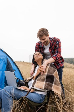 Photo for Multiethnic couple with blanket and laptop smiling at each other near tent on meadow - Royalty Free Image