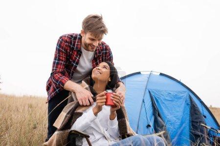 Photo pour Un homme souriant met une couverture sur une petite amie afro-américaine souriante avec une tasse près de la tente - image libre de droit