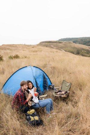 Photo pour Couple interracial souriant avec couverture et tasse assis près de la tente sur pelouse herbeuse - image libre de droit