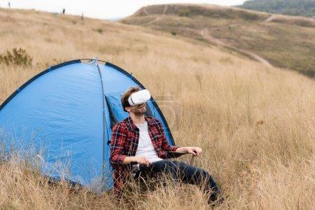 Photo pour Homme souriant utilisant un casque vr tout en étant assis près de la tente sur la pelouse - image libre de droit