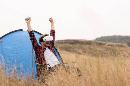 Photo pour Homme positif en réalité virtuelle casque montrant oui geste près de tente sur prairie - image libre de droit