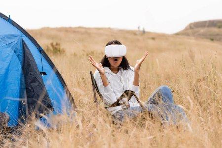 Photo pour Femme afro-américaine excitée utilisant un casque vr près de la tente sur prairie herbeuse - image libre de droit