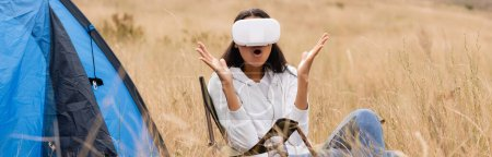 Excited african american woman using vr headset near tent and grass on blurred foreground, banner