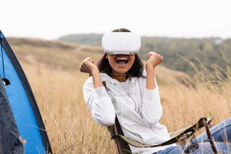 Fröhliche Afroamerikanerin mit Virtual-Reality-Headset auf Stuhl neben Zelt auf Feld