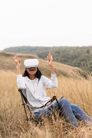 Cheerful african american woman with crossed fingers using  vr headset on chair in field