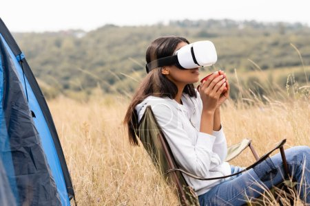 Smiling african american woman in vr headset holding cup while sitting on chair near tent on meadow