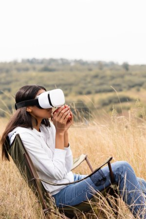 African american woman holding cup while using vr headset on chair and grassy meadow