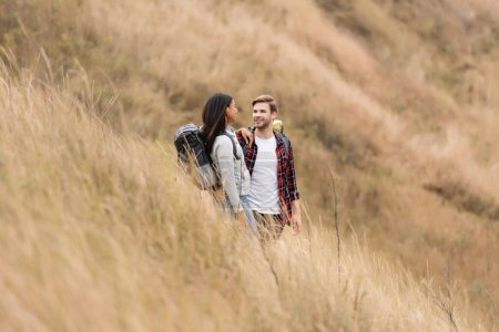 Photo for Smiling interracial couple with backpacks looking at each other on gassy hill - Royalty Free Image