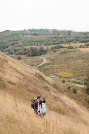 Photo for Smiling interracial couple with backpacks standing on hill with landscape at background - Royalty Free Image