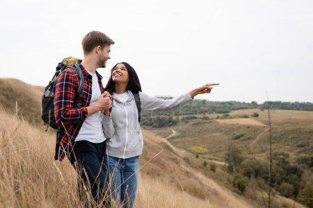 Photo pour Femme afro-américaine avec sac à dos pointant du doigt le paysage près du petit ami avec sac à dos - image libre de droit