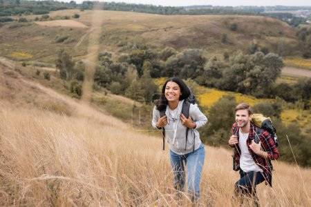 Photo for Interracial couple with backpacks walking on hill with grass during trip - Royalty Free Image