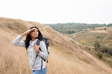 Photo for Smiling african american woman holding backpack and looking away during trip on hill - Royalty Free Image