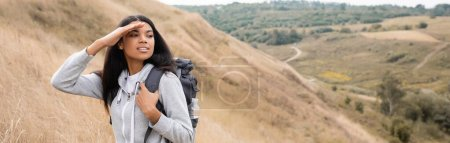Photo for Smiling african american hiker looking away while standing on hill during trip, banner - Royalty Free Image