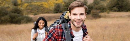 Photo pour Voyageur souriant avec sac à dos regardant loin près de petite amie afro-américaine sur fond flou pendant le voyage, bannière - image libre de droit