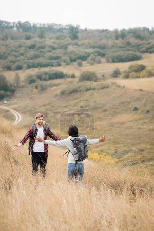 Photo pour Femme afro-américaine avec sac à dos debout avec les mains tendues près du petit ami sur une colline herbeuse - image libre de droit