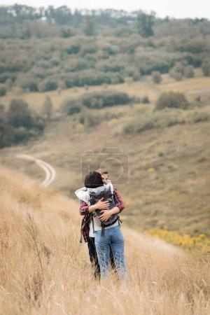 Photo pour Jeune homme embrassant petite amie avec sac à dos pendant le voyage sur la colline - image libre de droit