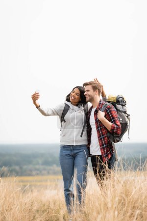 Smiling multiethnic travelers taking selfie with smartphone on meadow