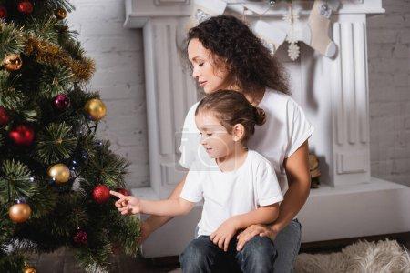 Mère et fille touchant boule de Noël sur le pin festif près de la cheminée