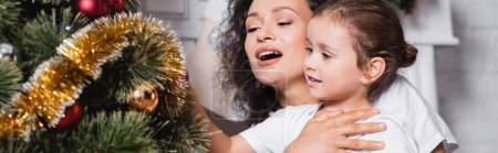 Photo for Panoramic shot of mother and daughter near festive pine at home - Royalty Free Image