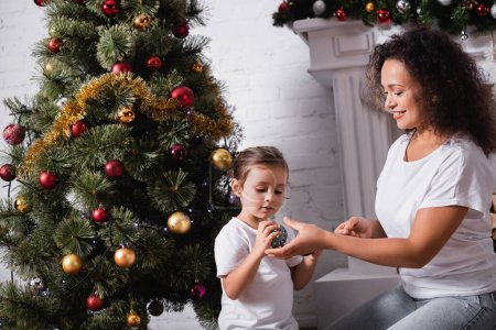 Photo for Mother and daughter with christmas balls sitting near decorated pine at home - Royalty Free Image