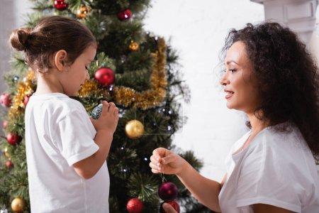 Photo pour Vue latérale de la mère et de la fille avec bal de Noël près de pin à la maison - image libre de droit