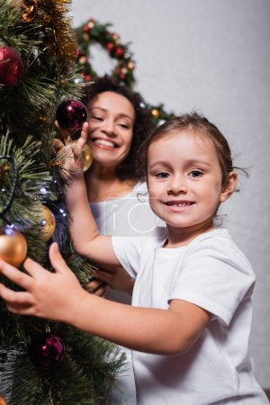 Photo for Selective focus of girl touching christmas balls on pine near mother at home - Royalty Free Image