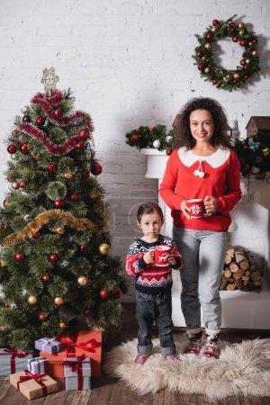 Photo pour Mère et fille avec des tasses debout près du pin festif et cheminée à la maison - image libre de droit
