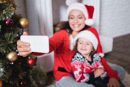 Selective focus of mother and daughter in santa hats taking selfie at home