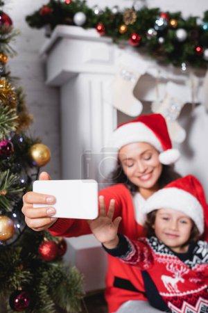 Photo pour Concentration sélective de la mère et de la fille prenant selfie près de la cheminée à la maison - image libre de droit