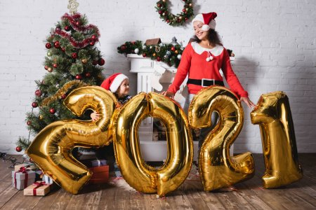 Photo for Daughter and mother in santa hats standing behind balloons with numbers - Royalty Free Image