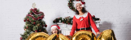 Photo for Panoramic shot of mother and daughter in santa hats standing near balloons - Royalty Free Image