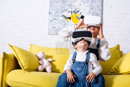 Photo for Daughter standing near mother in virtual reality headset at home - Royalty Free Image