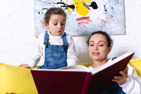 Fille excitée debout près de la mère tenant livre avec photo sur fond