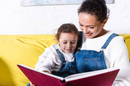 Mother embracing daughter reading book at home