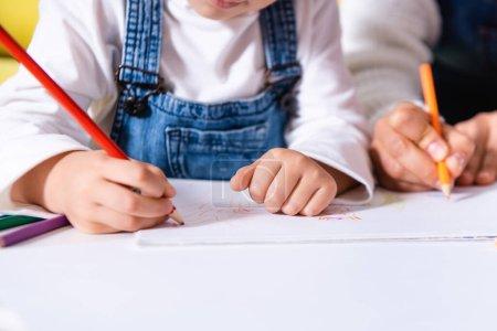 Photo pour Vue recadrée du dessin mère et fille avec crayons de couleur - image libre de droit