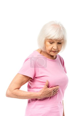 Elderly woman in pink t-shirt touching breast isolated on white