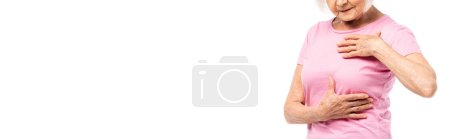 Photo for Panoramic shot of elderly woman in pink t-shirt touching breast isolated on white - Royalty Free Image