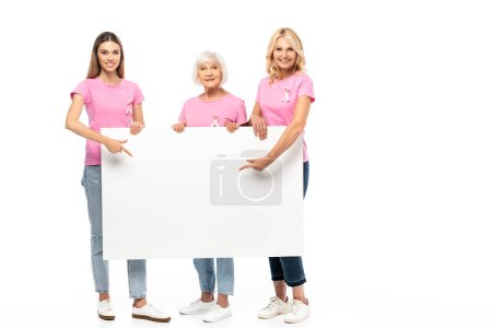 Women with ribbons of breast cancer awareness pointing at empty board on white background
