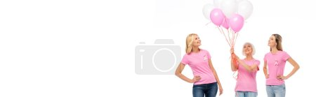Photo for Panoramic shot of women with pink ribbons looking at balloons isolated on white - Royalty Free Image